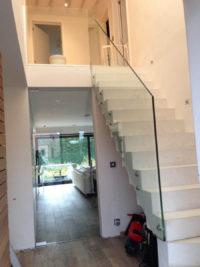 Glazen balustrade en trapwand